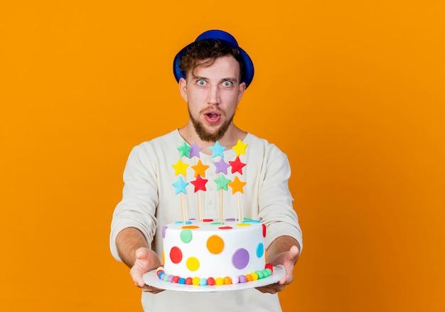 Onder de indruk jonge knappe slavische partij kerel met feestmuts kijken camera uitrekken van verjaardagstaart met sterren naar camera geïsoleerd op een oranje achtergrond met kopie ruimte