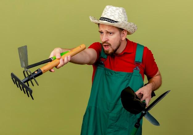 Onder de indruk jonge knappe slavische tuinman in uniform en hoed houden en strekken tuinman tools op zoek rechtstreeks geïsoleerd op olijfgroene muur