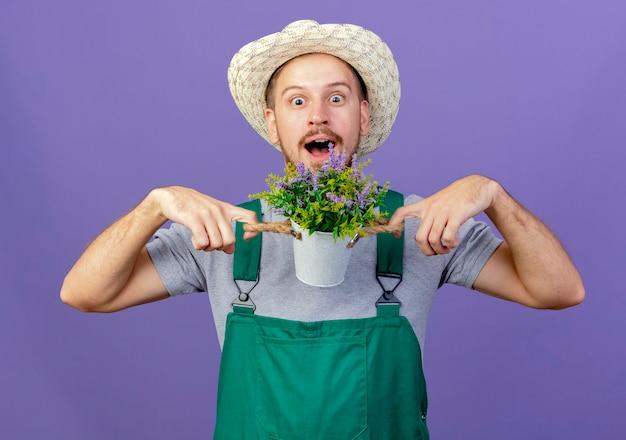 Onder de indruk jonge knappe slavische tuinman in uniform en hoed met bloempot geïsoleerd op paarse muur