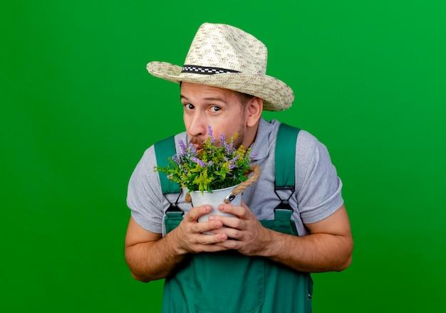 Onder de indruk jonge knappe slavische tuinman in uniform en hoed met bloempot op zoek geïsoleerd op groene muur met kopie ruimte