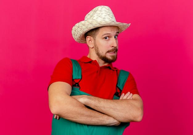 Onder de indruk jonge knappe slavische tuinman in uniform en hoed staande met gesloten houding geïsoleerd op karmozijnrode muur met kopie ruimte