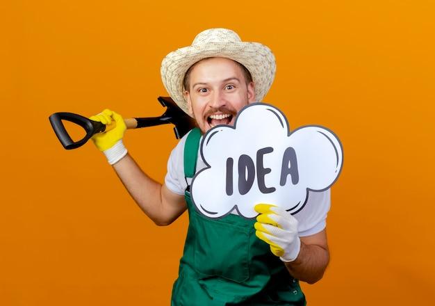 Onder de indruk jonge knappe slavische tuinman in uniform met hoed en tuinhandschoenen met schop en idee-zeepbel op zoek geïsoleerd