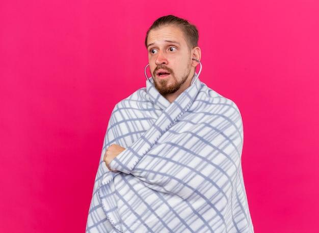 Onder de indruk jonge knappe slavische zieke man met een stethoscoop gewikkeld in plaid kijken naar kant geïsoleerd op roze muur met kopie ruimte Gratis Foto