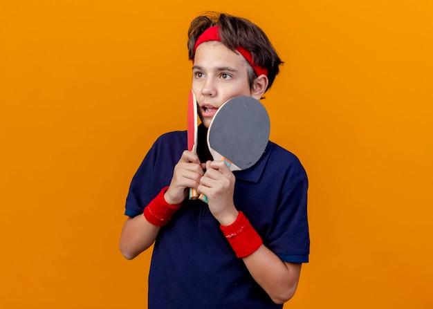 Onder de indruk jonge knappe sportieve jongen die hoofdband en polsbandjes met beugels draagt die pingpongrackets aanraken van gezicht met hen geïsoleerd op een oranje achtergrond met kopie ruimte