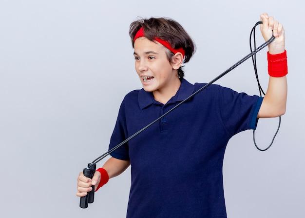 Onder de indruk jonge knappe sportieve jongen die hoofdband en polsbandjes met beugels draagt die recht op zoek zijn naar springtouw geïsoleerd op een witte achtergrond met kopie ruimte