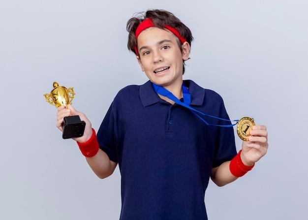 Onder de indruk jonge knappe sportieve jongen die hoofdband en polsbandjes met beugels en medaille rond de nek draagt ?? die medaille en winnaar beker houdt kijken naar camera geïsoleerd op witte achtergrond