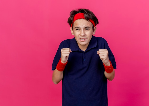 Onder de indruk jonge knappe sportieve jongen met hoofdband en polsbandjes met beugels kijken naar de voorkant balde vuisten geïsoleerd op roze muur met kopie ruimte