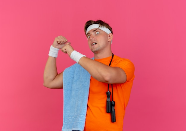 Onder de indruk jonge knappe sportieve man met handdoek om de nek en springtouw op schouder met hoofdband en polsbandjes wijzend achter geïsoleerd op roze