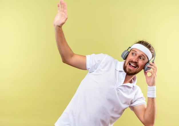 Onder de indruk jonge knappe sportieve man met hoofdband en polsbandjes en koptelefoon die hand opsteekt en naar de zijkant kijkt met de hand op koptelefoon geïsoleerd op groene muur met kopieerruimte