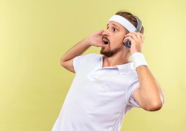 Onder de indruk jonge knappe sportieve man met hoofdband en polsbandjes en koptelefoon kijkend naar kant met handen op koptelefoon geïsoleerd op groene muur met kopieerruimte