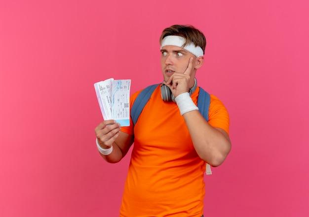 Onder de indruk jonge knappe sportieve man met hoofdband en polsbandjes en rugtas met koptelefoon op nek met vliegtuigkaartjes hand op gezicht kijkend naar kant