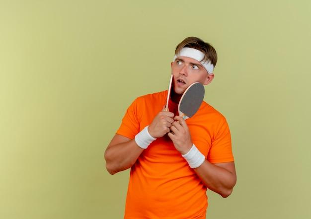 Onder de indruk jonge knappe sportieve man met hoofdband en polsbandjes houden pingpong rackets en aanraken van gezicht met hen kijken naar kant geïsoleerd op olijfgroen