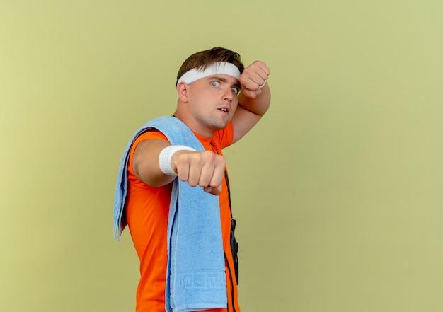 Onder de indruk jonge knappe sportieve man met hoofdband en polsbandjes met handdoek op de schouder en springtouw rond de nek uitrekkende vuist geïsoleerd op olijfgroen