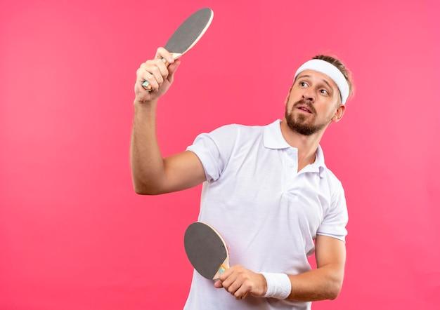 Onder de indruk jonge knappe sportieve man met hoofdband en polsbandjes met pingpongrackets en kijken naar hen geïsoleerd op roze muur met kopieerruimte