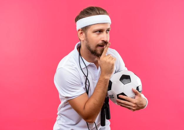 Onder de indruk jonge knappe sportieve man met hoofdband en polsbandjes met voetbal gebaren stilte en kijken naar kant met springtouw om zijn nek geïsoleerd op roze muur