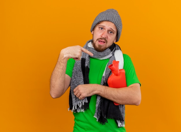Onder de indruk jonge knappe zieke man met muts en sjaal houden en wijzend op warm waterzak kijken naar voorzijde geïsoleerd op oranje muur