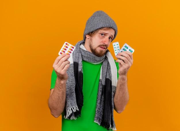 Onder de indruk jonge knappe zieke man met muts en sjaal met pakken van capsules kijken naar voorzijde geïsoleerd op oranje muur