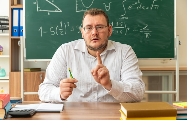 Onder de indruk jonge leraar met een bril die aan het bureau zit met schoolbenodigdheden in de klas met telstokken die naar de voorkant kijken en de vinger opsteken