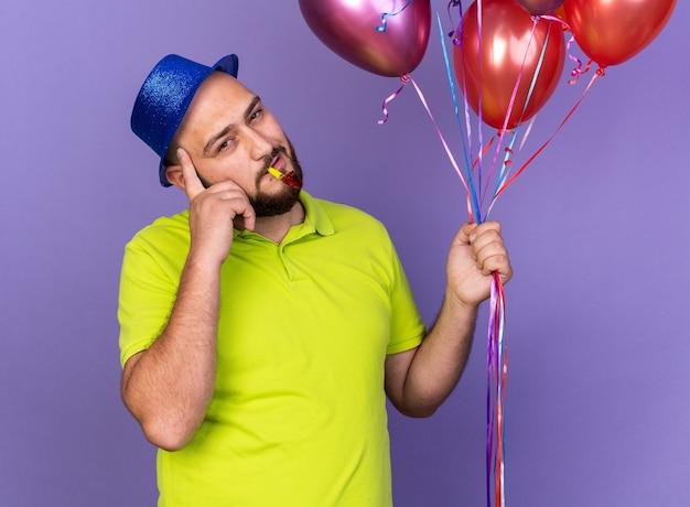 Onder de indruk jonge man met feesthoed met ballonnen die feestfluitje blazen en vinger op tempel zetten