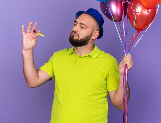 Onder de indruk jonge man met feestmuts die ballonnen vasthoudt en naar een fluitje in zijn hand kijkt