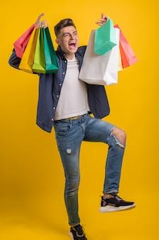 Onder de indruk jonge man met kleurrijke boodschappentassen in handen met open mond