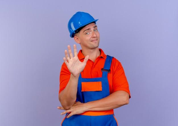 Onder de indruk jonge mannelijke bouwer die eenvormig en veiligheidshelm draagt die vijf toont
