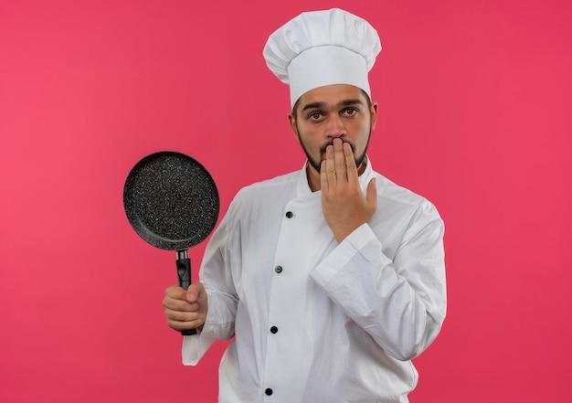 Onder de indruk jonge mannelijke kok in chef-kok uniform met koekenpan en hand op de mond geïsoleerd op roze muur on