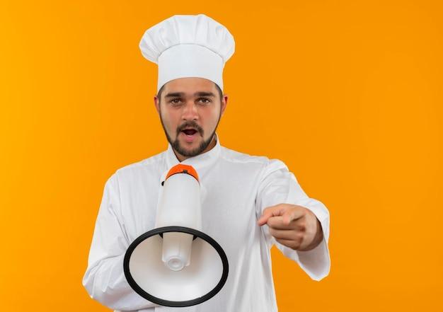 Onder de indruk jonge mannelijke kok in chef-kok uniform praten door spreker en wijzend geïsoleerd op oranje muur met kopieerruimte