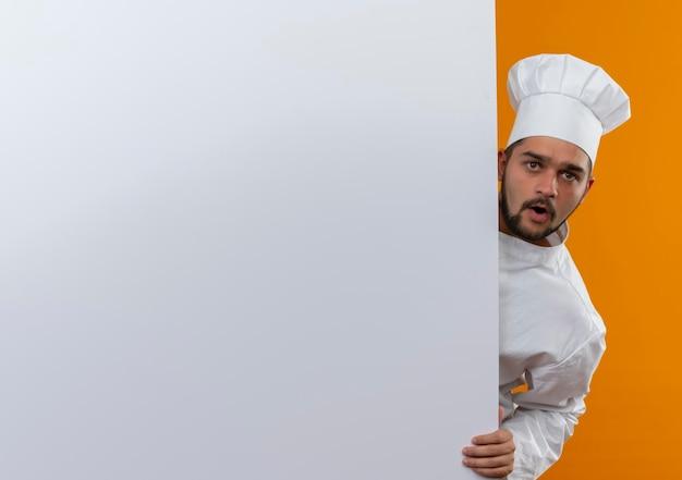 Onder de indruk jonge mannelijke kok in uniform van de chef-kok die van achteren kijkt en hand op een witte muur legt die op een oranje muur is geïsoleerd met kopieerruimte
