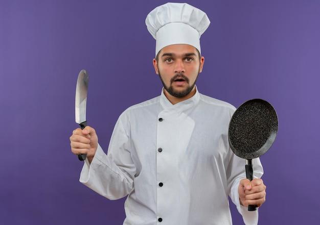 Onder de indruk jonge mannelijke kok in uniform van de chef-kok met hakmes en koekenpan geïsoleerd op paarse muur