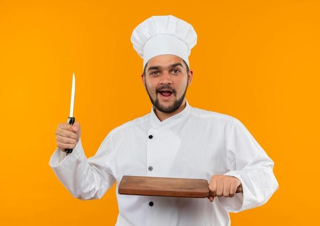 Onder de indruk jonge mannelijke kok in uniform van de chef-kok met mes en snijplank geïsoleerd op oranje muur