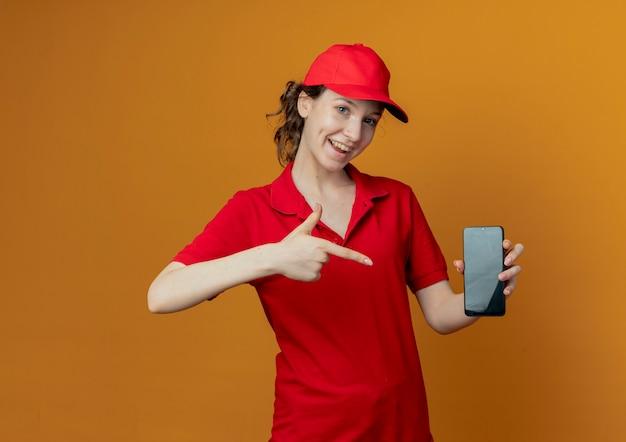 Onder de indruk jonge mooie bezorger in rood uniform en pet tonen en wijzend op mobiele telefoon