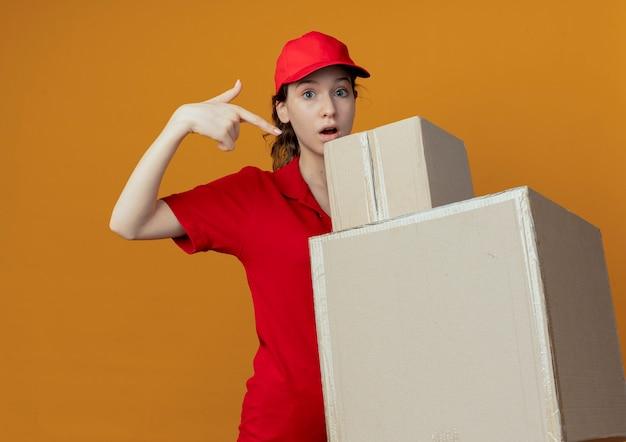 Onder de indruk jonge mooie bezorger in rood uniform en pet vasthoudend en wijzend op kartonnen dozen