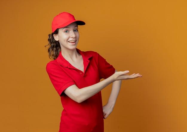 Onder de indruk jonge mooie bezorger in rood uniform en pet wijzend met de hand naar de zijkant