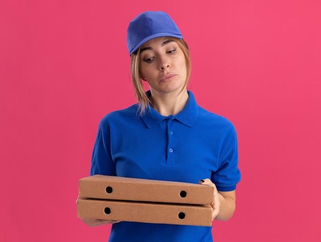 Onder de indruk jonge mooie bezorger in uniform houdt en kijkt naar pizzadozen op roze