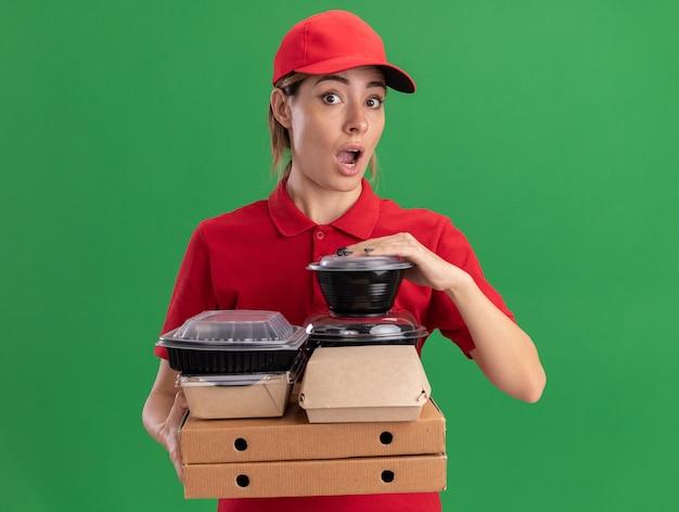 Onder de indruk jonge mooie bezorger in uniform houdt papieren voedselpakketten en containers op pizzadozen geïsoleerd op groene muur