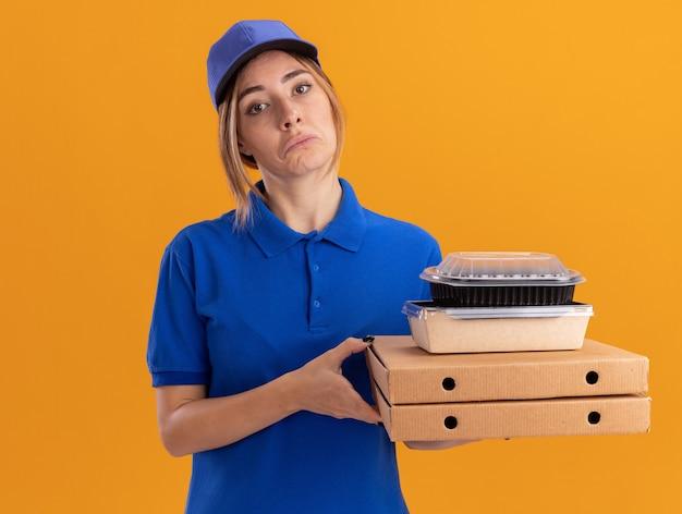 Onder de indruk jonge mooie bezorger in uniform houdt papieren voedselpakketten en containers op pizzadozen op oranje
