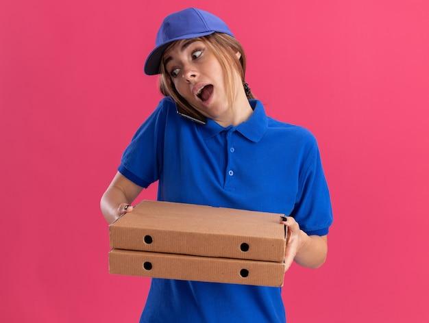 Onder de indruk jonge mooie bezorger in uniform houdt pizzadozen en praat over de telefoon op roze