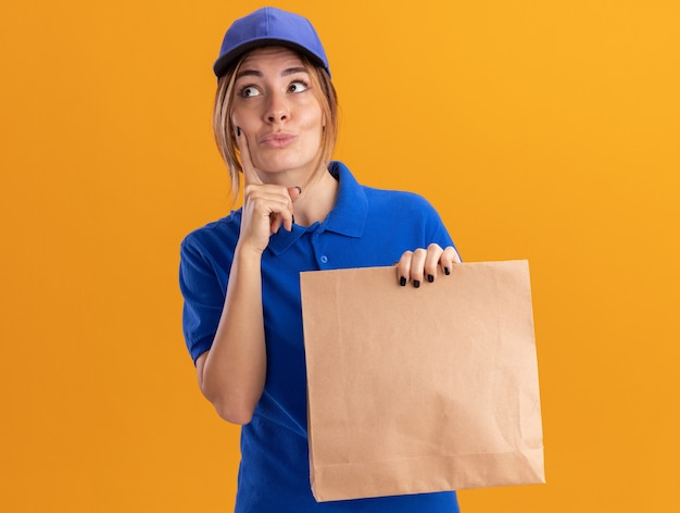 Onder de indruk jonge mooie bezorger in uniform legt vinger op gezicht en houdt papieren pakket op zoek naar kant geïsoleerd op oranje muur