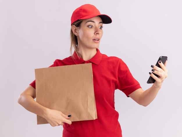 Onder de indruk jonge mooie bezorgvrouw in uniform houdt papieren pakket en kijkt naar telefoon geïsoleerd op een witte muur