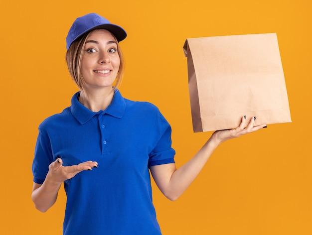 Onder de indruk jonge mooie bezorgvrouw in uniforme ruimen en punten op papierpakket met hand geïsoleerd op oranje muur