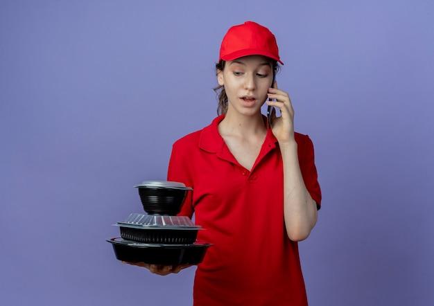 Onder de indruk jonge mooie levering meisje dragen rode uniform en pet houden en kijken naar voedselcontainers en praten over telefoon geïsoleerd op paarse achtergrond met kopie ruimte