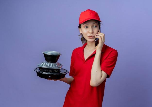 Onder de indruk jonge mooie levering meisje dragen rode uniform en pet kijken kant houden van voedsel containers en praten over telefoon geïsoleerd op paarse achtergrond met kopie ruimte
