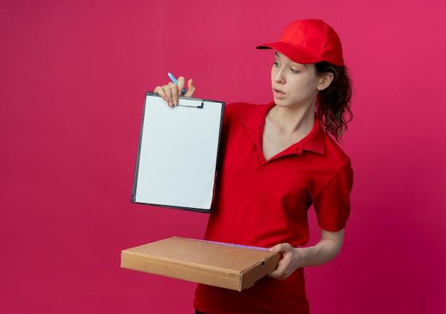Onder de indruk jonge mooie levering meisje in rood uniform en pet houden pizza pakket pen en tonen klembord kijken naar klembord geïsoleerd op karmozijnrode achtergrond met kopie ruimte