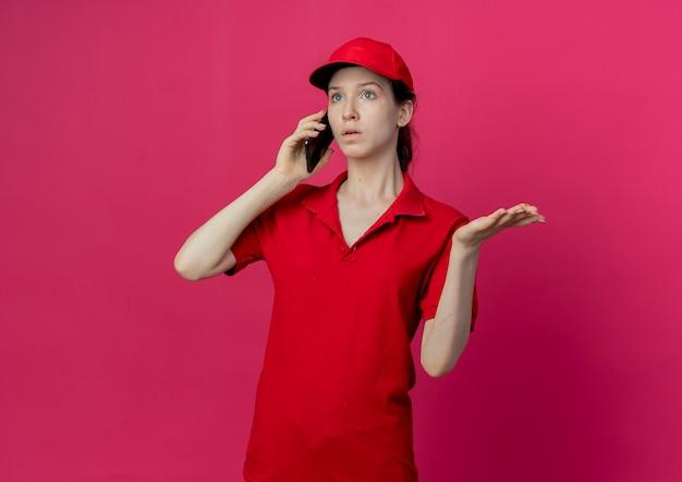 Onder de indruk jonge mooie levering meisje in rood uniform en pet praten over de telefoon op zoek rechtdoor en tonen lege hand geïsoleerd op karmozijnrode achtergrond met kopie ruimte