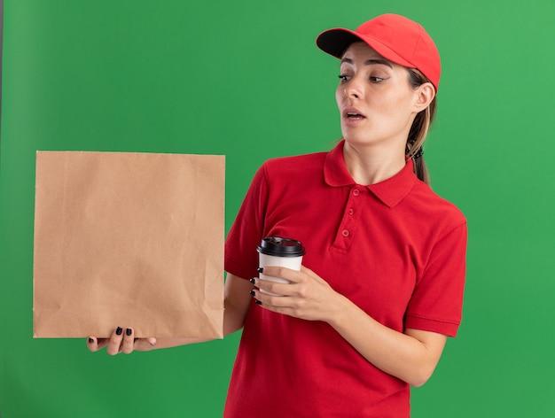 Onder de indruk jonge mooie levering meisje in uniform houdt papier beker en kijkt naar papier pakket op groen