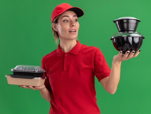 Onder de indruk jonge mooie levering meisje in uniform houdt voedselpakketten en kijkt naar voedselcontainers op groen