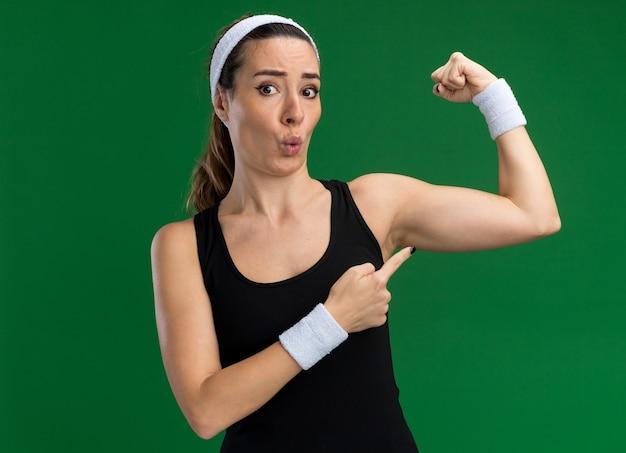 Onder de indruk jonge mooie sportieve vrouw met hoofdband en polsbandjes kijkend naar voren doen sterk gebaar wijzend op haar spieren geïsoleerd op groene muur
