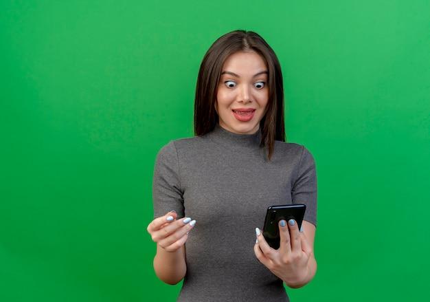 Onder de indruk jonge mooie vrouw die en mobiele telefoon houdt bekijkt en hand in lucht houdt die op groene achtergrond met exemplaarruimte wordt geïsoleerd