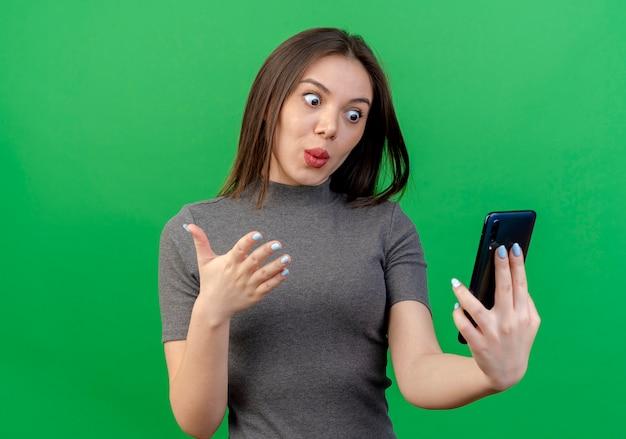 Onder de indruk jonge mooie vrouw die en mobiele telefoon houdt bekijkt en hand in lucht houdt die op groene achtergrond wordt geïsoleerd